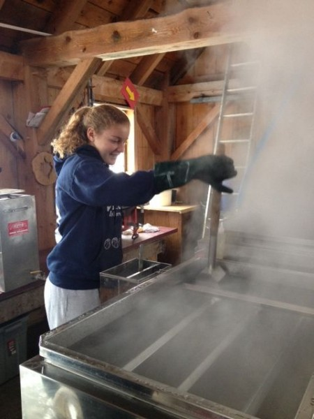 A student at Fairfield Center School boils sap to make Maple Syrup in the school's sugar house.