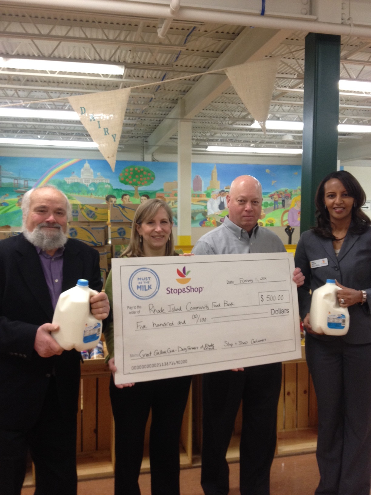 Dairy Farmer Louis Escobar of Escobar's Highland Farm, Rhode Island Community Food Bank's Chief Philanthropy Officer Lisa Roth Blackman and Director of Procurement Bruce Zarembka, and Stop & Shop #722 Providence Store Manager Hilina Ajakaiye celebrate the results of the Great Gallon Give